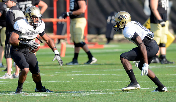 Ray Polk (7) tries to run around Jeffrey Hall (16)during the University of Colorado football team practice on Tuesday August 21 , 2012.<br /> For more photos go to www.buffzone. com<br /> Photo by Paul Aiken