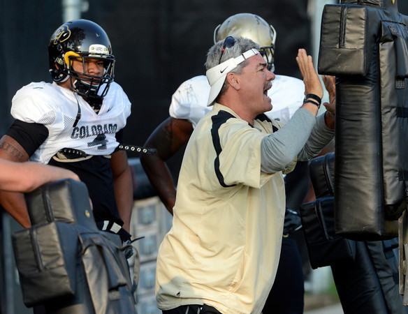 Assistant Coach Brian Cabral demonstrates the proper technique for hitting the sled during the University of Colorado football team practice on Tuesday August 21 , 2012.<br /> For more photos go to www.buffzone. com<br /> Photo by Paul Aiken