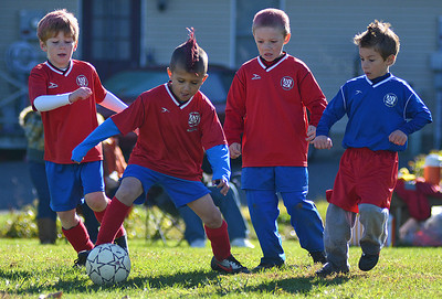 Hunter Kisella, 8 of Dornsife, center, plays U-8 AYSO soccer in Selinsgrove on Saturday morning. Kisella, along with seven of his teammates, spray-painted their hair pink in support of Breast Cancer Awareness Month. Kisella is unsure how much he likes the color pink but he does think it will help him play better.