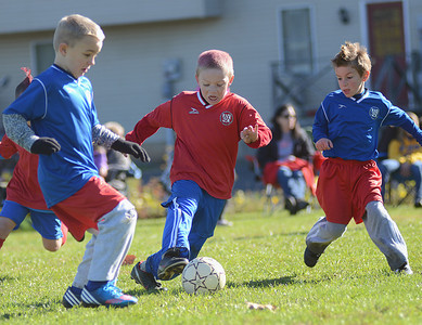 Travis Feese, 7 of Trevorton, center, attacks the ball during a U-8 AYSO soccer game in Selinsgrove on Saturday morning. Feese, along with seven of his teammates, spray-painted his hair pink for the game in support of Breast Cancer Awareness month.