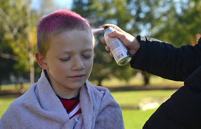 "Travis Feese, 7 of Trevorton, has his hair spray-painted pink by Nikki Kisella, of Dornsife, before his U-8 AYSO game in Selinsgrove on Saturday morning. He said that ""it kinda tickles a little bit"" when the paint is put on his hair. Feese also said it was ""kinda cool"" to have the team all paint their hair pink."