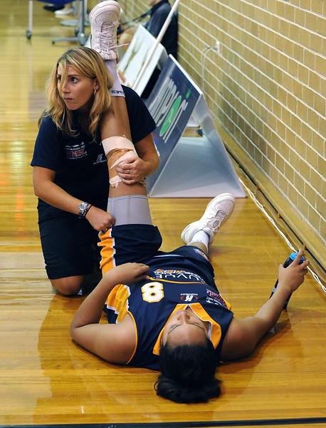 The team physio helps Eva stretch her quads.