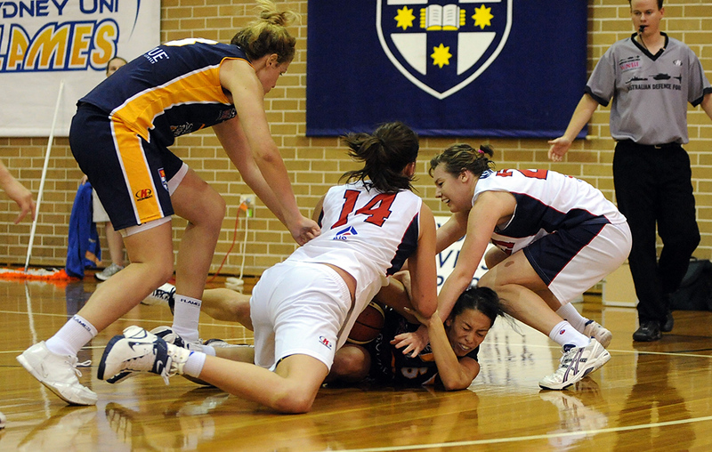 Alicia Poto cops a knee to the back of her head as she refuses to let go of the ball.