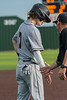 After arriving safely at third base after a bad throw to pick him off at first, #7 Aledo shortstop Sam Sisk gets a low five from Coach Barry.