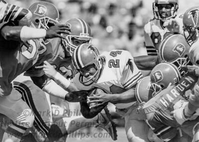 Atlanta Falcons running back Joe Washington is swarmed by Denver Broncos during a 44-28 loss on September 22, 1985 at Atlanta-Fulton County Stadium, Atlanta, GA.