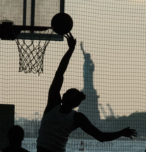 Basketball at Brooklyn Bridge Park in silhouette with the Statue of Liberty