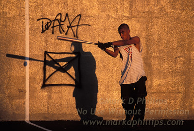 A young man swings at a pitch with his shadow on the wall of a school playground in Carroll Gardens, Brooklyn, near the Gowanus Canal.