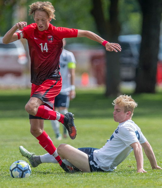 Cam Jolley (14) jumps over the Layton defenders slide tackle during the 5-A playoff game at Layton High school on May 19, 2017.