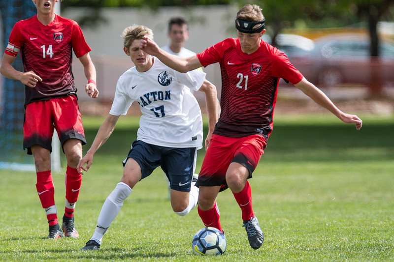 American Fork's Parker Draney (21) tries to maintain possession of the ball as Layton High's Garrett Boston (17) trails the offensive player at Layton High school on May 19, 2017. Layton would end up overcoming American Fork 4-1.