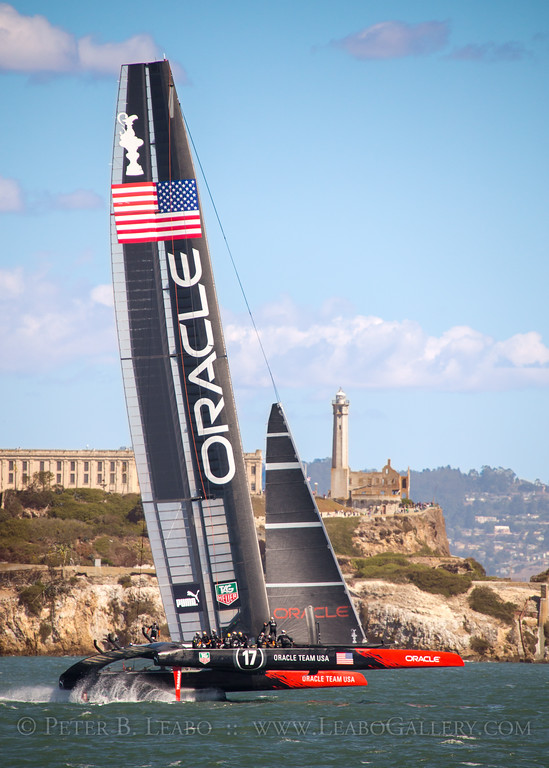 Oracle Team USA rides on foils as it flies past Alcatraz Island in San Francisco Bay in the final reace of the 34th Americas Cup