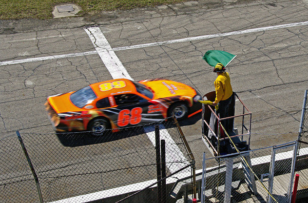 A CRA Late Model Sportsman takes the green flag from Official Starter Gary Mong during practice on the opening day at Anderson Speedway.