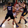 MARY SCHWALM/Staff photo Central Catholic's Courtney Walsh drives between Andover defenders Jessica Witten (12) and Alyssa Casey, left, during their basketball game in Lawrence. 1/9/14