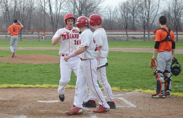 Neoga's Riley Walk (10) is congratulated at home plate by teammates Zach Monroe (left) and Kenton Albin (right), while catcher Aaron Goeckner (4) looks out at pitcher Cole Borders (5) in Neoga.