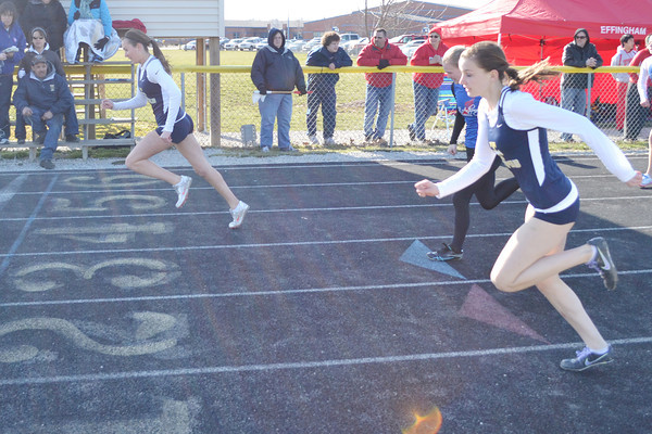Teutopolis' Morgan Drees (left) takes first in the 100-meter hurdles, while teammate Ellie Wessel (front) and St. Anthony's Kassy Dammerman (back) race toward the finish behind her.