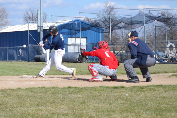 Teutopolis' Chase Wendling takes a cut at a pitch from Effingham's Preston Walker (not shown), while Effingham's Carter Hayes prepares behind the plate.
