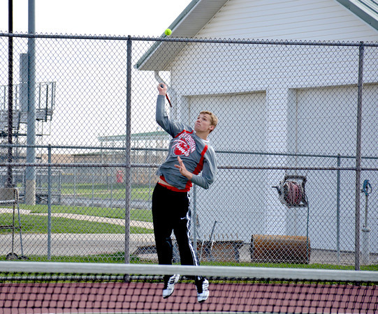 Effingham's Isaac Foreman jumps and serves during a dual match in singles play against Olney.