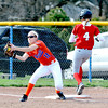 Newton's Megan Probst stretches and catches an incoming throw at first base, seconds too late as a Marshall runner reaches safely.