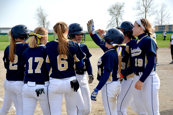 Teutopolis' Kadi Borries (center) is congratulated at home plate by a group of teammates after a home run against Stew-Stras/Windsor.