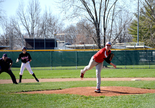 Effingham's Ryan Barnes delivers a pitch while a runner from Highland takes a lead off second base behind him.