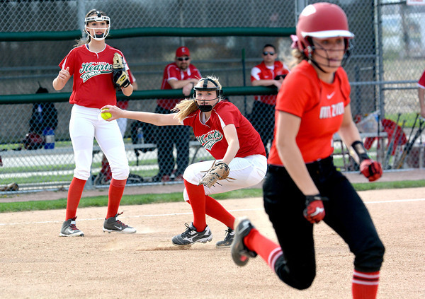 Effingham's Hope Collier picks up a ground ball as a Mt. Zion runner heads to first base during an Apollo Conference doubleheader.