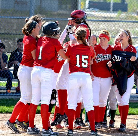 Effingham's Brittany Beals (center) jumps into a group of teammates and steps on home plate after hitting a solo home run against Altamont.