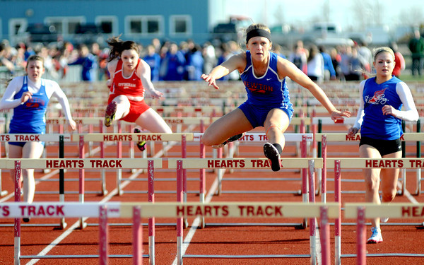 Newton's Mckendra Barthelme strides over a hurdle in winning the first heat of the women's 100-meter hurdles at Effingham High School.