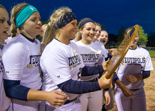 Members of the Teutopolis softball team gaze at the Cross Creek Classic trophy after defeating St. Anthony 11-1.