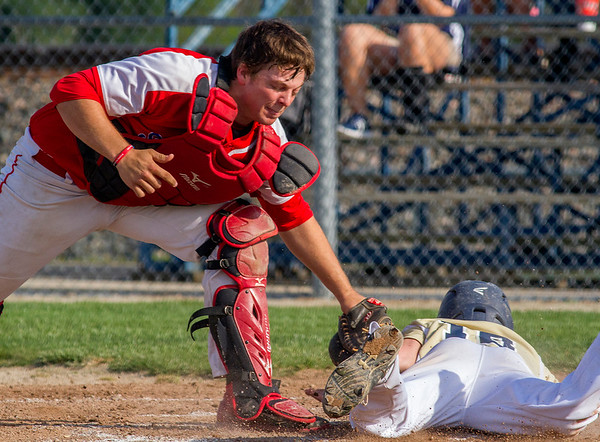 St. Anthony catcher Greg Utz makes the tag out at home on Teutopolis courtesy runner Jared Bloemer in the bottom of the second inning. The defensive play was just one of many that helped the Bulldogs secure a 7-2 win.