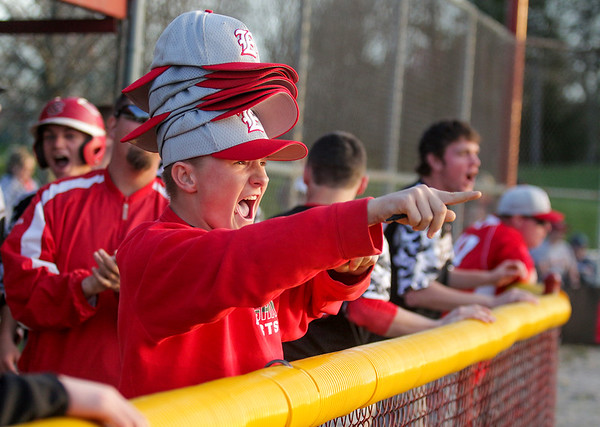 Effingham's Patrick Sherrod, wearing a number of extra hats as a rally cap, points to the field after Bryce Lohman's game-winning hit during the Flaming Hearts' comeback win over Charleston.