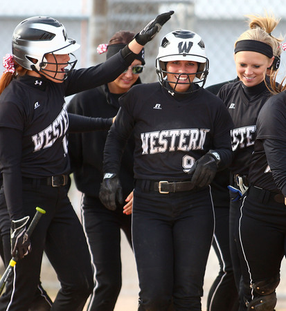4-24-14<br /> Western vs. Northwestern softball<br /> Western's Jenna Wiechmann is congratulated by her teammates at home base after she hit a home run.<br /> Kelly Lafferty | Kokomo Tribune