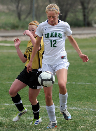 """Hannah Driscoll (12) of Niwot controls the ball past the Arapahoe defender.<br /> For more photos of the game, go to  <a href=""""http://www.dailycamera.com"""">http://www.dailycamera.com</a><br /> Cliff Grassmick / April 14, 2012"""