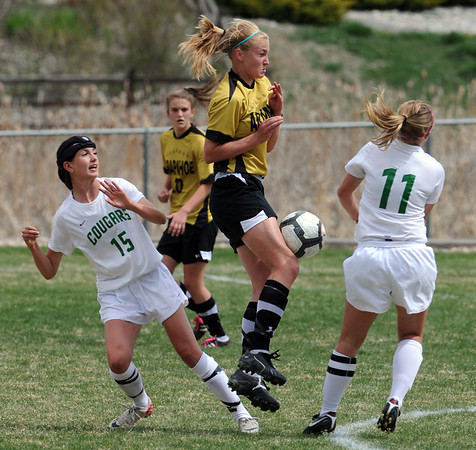 "Stacey Lukasiewicz, center,  of Arapahoe, tries to keep the ball from Maria Fayeulle (15)  and Kylie Fischer, both of Niwot.<br /> For more photos of the game, go to  <a href=""http://www.dailycamera.com"">http://www.dailycamera.com</a><br /> Cliff Grassmick / April 14, 2012"