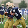 HALEY WARD | THE GOSHEN NEWS<br /> Safety Max Redfield goes to tackle cornerback Jesse Bongiovi duringa drill at Notre Dame football practice Saturday.