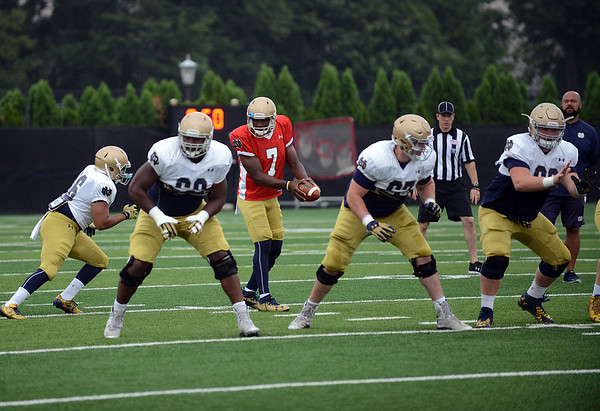 HALEY WARD | THE GOSHEN NEWS<br /> Quarterback Brandon Wimbush looks to hand off the ball while the offensive line prepares to block while running drills during Notre Dame football practice Saturday.