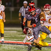 The Berries Drake McLochlin (5) breaks a run down the field in the second half with the Mavericks Kaden Rice hanging on for the ride. Logansport fell to McCutcheon by a score of 21-0 on Friday night.