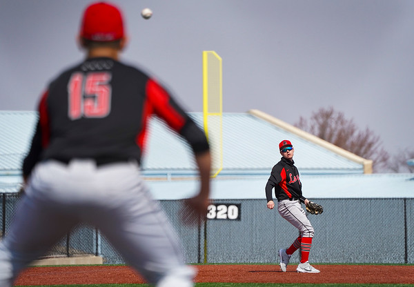 Logansport Berries shortstop Gavin Smith (23) throws to first baseman Grayson Long (15) during the first game of a doubleheader between the Logansport Berries and LaPorte Slicers on Saturday, April 3, 2021 in Logansport.