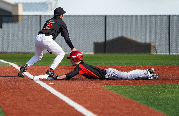 Logansport Berries outfielder Calryan Parmeter (8) slides to third base as LaPorte Slicers' Carter Moses (5) awaits a throw from the outfield during the first game of a doubleheader between the Logansport Berries and LaPorte Slicers on Saturday, April 3, 2021 in Logansport.