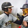 Two Peru Tigers high five after scoring a run during the first inning of a game between the Logansport Berries and Peru Tigers on Friday, April 23, 2021 in Logansport.