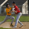 Tri-County Cavaliers infielder Dylan Matthew (11) tags Pioneer Panthers infielder Noah Pearson (20) after Pearson was caught in a pickle during the second inning of a game between the Tri-County Cavaliers and Pioneer Panthers on Tuesday, April 6, 2021 in Royal Center.