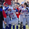 Caston Comets pitcher Addison Zimpleman (9) is greeted by teammates at home plate after hitting a home run during the season opener between the Caston Comets and Carroll Cougars on Friday, April 2, 2021 in Fulton.