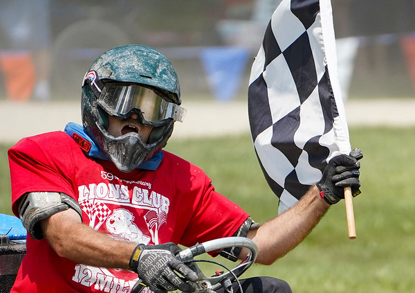 John Troyer takes a lap with the checkered flag after winning the Twelve Mile 500's Briggs Race at Plank Hill Park in Twelve Mile on Sunday, July 4, 2021.