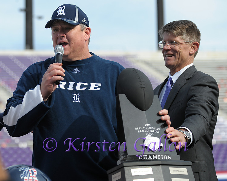 John Garrison helps hold the Bell Helicopter Trophy as Rice Head Coach David Bailiff thanks the crowd.