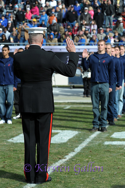 Marine General Whistler conducts the official swearing in of new recruits during halftime.