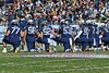 Navy players kneel and hold hands while waiting for the outcome of an injured teammate.