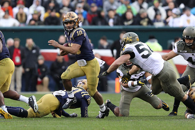 Navy quarterback #10 Malcolm Perry carries the ball past Army defenders.