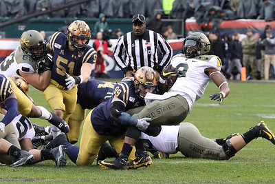 Navy nose guard #99 Jackson Pittman tackles Army fullback #3 Sandon McCoy.