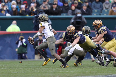 Army quarterback #13 Christian Anderson evades a leaping tackle attempt by Navy left end #96 Jackson Perkins.
