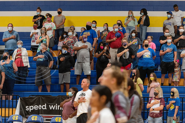 People attending the varisty volleyball game between Arp High School and Chapel Hill at Chapel Hill High School in Tyler wear face masks and social distance as the stand for the National Anthem on Tuesday, Aug. 11, 2020. The school enforced a reduced 50 percent capacity in the gymnasium as well as blocking off every other row in the bleachers for seating and requiring face masks.