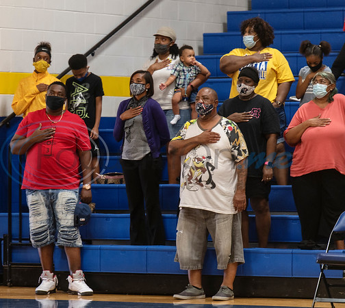 People attending the varsity volleyball game between Arp High School and Chapel Hill at Chapel Hill High School in Tyler wear face masks and social distance as the stand for the National Anthem on Tuesday, Aug. 11, 2020. The school enforced a reduced 50 percent capacity in the gymnasium as well as blocking off every other row in the bleachers for seating and requiring face masks.