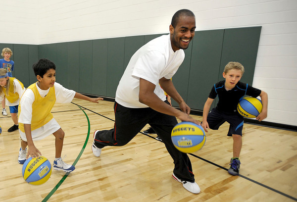 "Arron Afflalo, center, an NBA player of the Denver Nuggets, dribbles the ball during an exercise with from left, Tanish Jagtap, 10 of Boulder, and Coby Grant-Krent, 10, of Boulder. Afflalo came to visit a kids basketball camp Tuesday morning to sign autographs, play and talk with the kids. August 7, 2012. Rachel Woolf/ For the Daily Camera. For more photos, go to  <a href=""http://www.dailycamera.com"">http://www.dailycamera.com</a>."